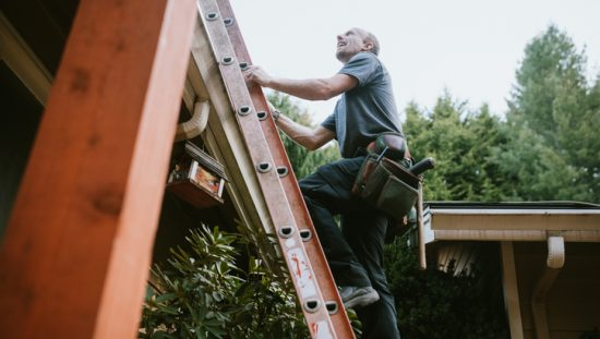 Man climbing ladder with three points of contact following safe inspection and environmental considerations.