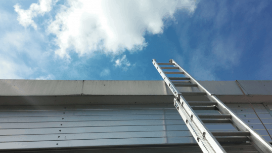 Metal extension ladder leading up to blue sky for safety.