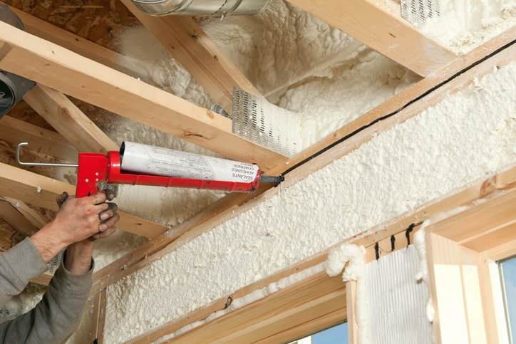 Worker caulks gap in home to mitigate radon entry in accordance with ANSI/AARST standards.
