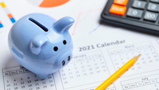Blue piggy bank on 2021 calendar for financial planning of ASTM E2659 accredited certificate issuer programs.