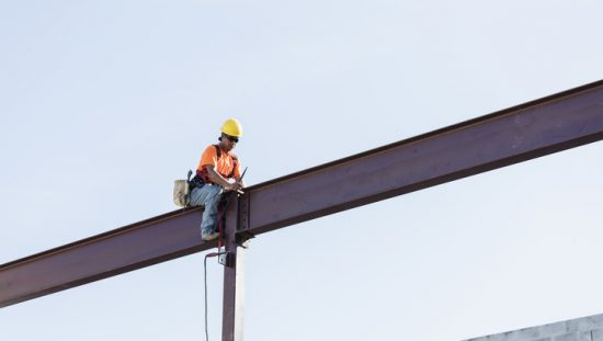 Worker sitting on girder and held safe by ANSI/ASSP Z359.11-2021 full body harness in the sky.