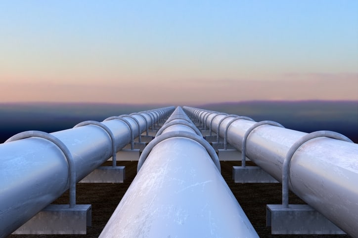 Three white pipelines transporting gas out past the ocean.
