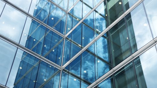 Flat glass exterior of blue corporate building that has been quality tested to ASTM C1036-21.