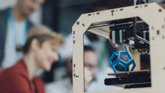 Group in background formatting ISO/ASTM 52915:2020 additive manufacturing file format (AMF) to print blue hexagon.