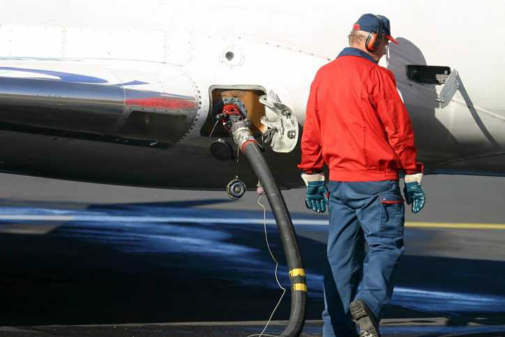 Man in old red windbreaker pumping jet fuel in plane to ASTM D1566-21 specifications.