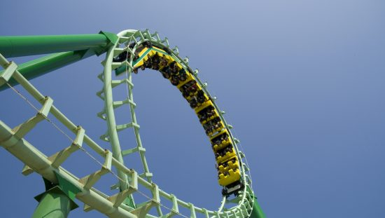 Green roller coaster loop providing ASTM F2291-21 amusement ride patrons with safe thrills.