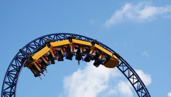 Roller coaster twisting patrons in yellow cars in the sky that was designed by following ASTM F2291-21.