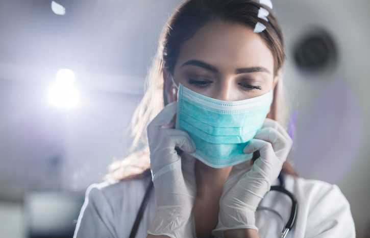 Young female doctor wearing medical face mask adhering to ASTM F2100-21 before surgery.